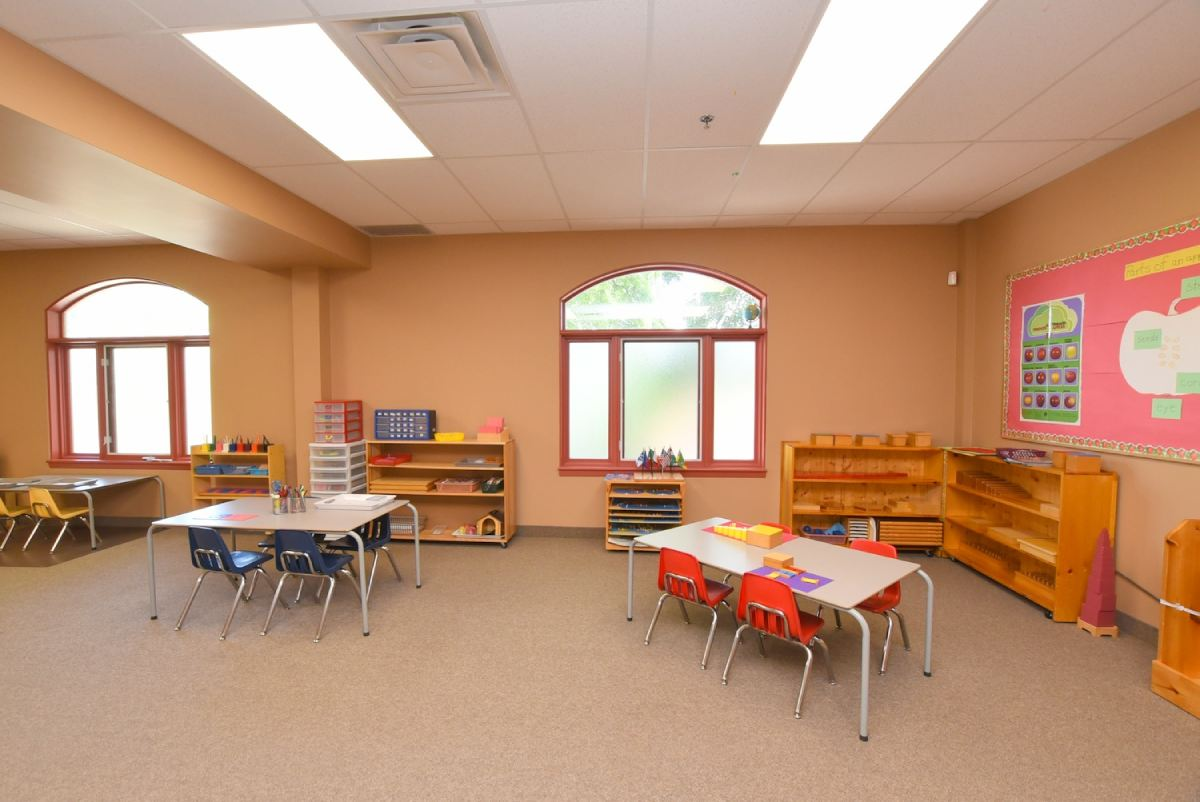 a preschool classroom with tables and chairs